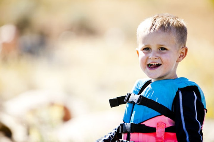 John Priebe, a 3 year old boy stands in a life jacket on the shores of Bear Lake, Utah.