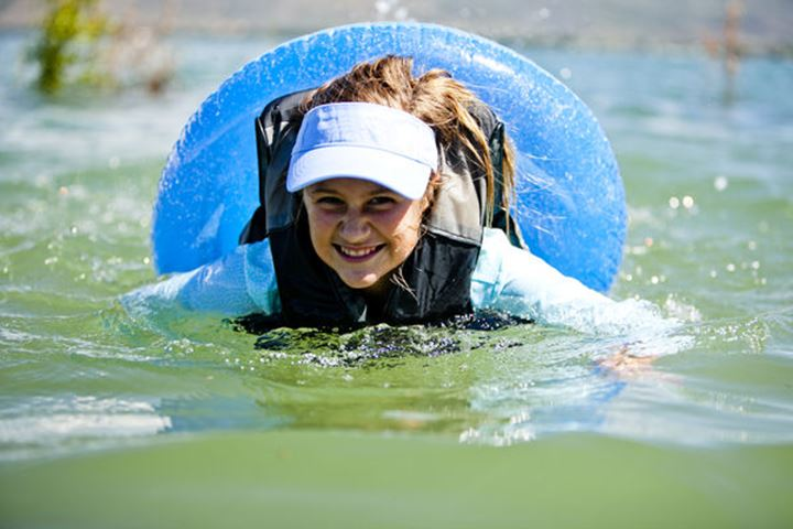 Anna Priebe floats and swims on an inner tube, Bear Lake.