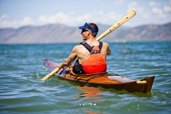 Tom Glass paddles a wooden kayak in Bear Lake, Utah.