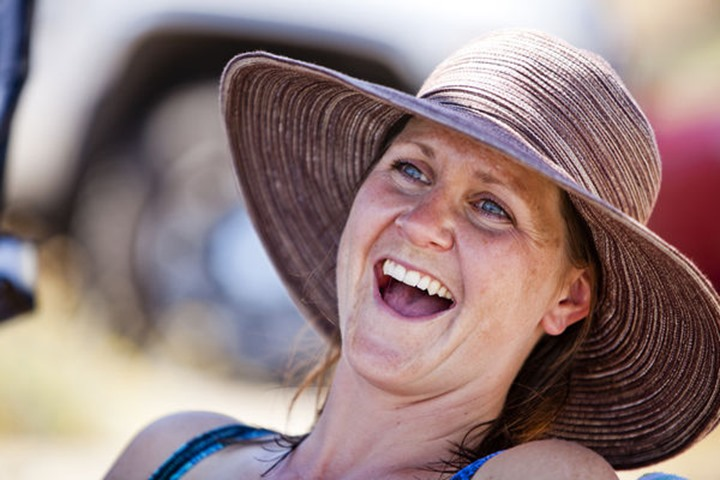 Kristen Priebe laughs while wearing a sunhat on the shore of Bear Lake.