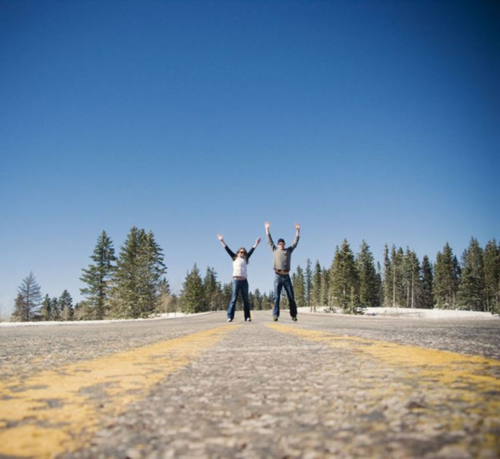 Two young tourists celebrate reaching the 10,000 foot summit of Route 64 through the Carson National Forest, New Mexico.