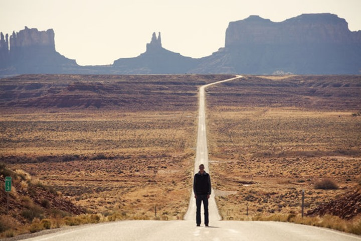 A traveler pauses for a picture on the stretch of road leading to Monument Valley, Utah. This scene has become an icon of the American west.