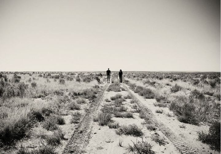 A young couple stands in the desert scrub near Cuba, New Mexico.