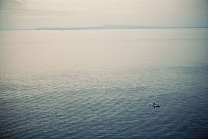 A fisherman works in his small boat in the bay of Naples, off the coast of Sorrento Italy.