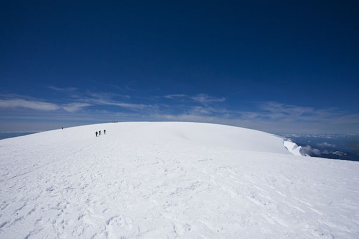The summit of Mt. Baker in the Cascades of Washington on a blue sky day with people in the distance.