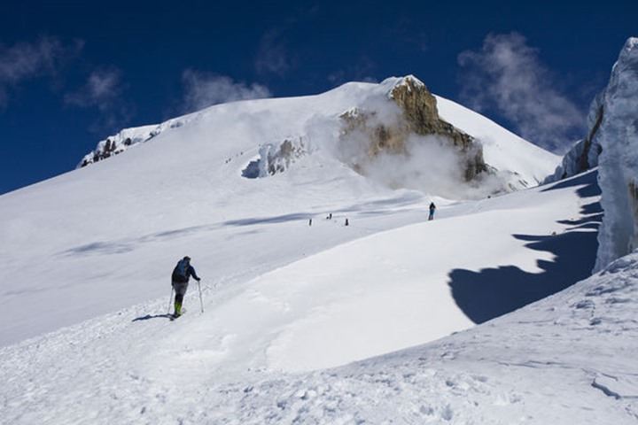 Skiers skin up a snowy ridge at sunrise on a blue bird day on Mt. Baker in Cascades of Washington.