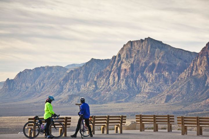 Two cyclists are admiring the view while taking a break, Red Rock Canyon National Conservation Area on 18th November 2011, Nevada, USA.