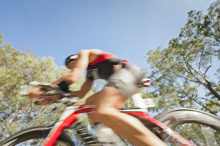 A Triathlete is cycling during the Noosa Triathlon on October 30, 2011, Noosa Heads, Queesland, Australia. (Blurred motion)