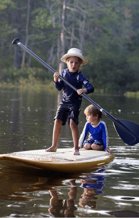 A six-year-old boy rides a stand-up paddleboard with his four-year-old brother on Otter Lake in Greenfield, New Hampshire.