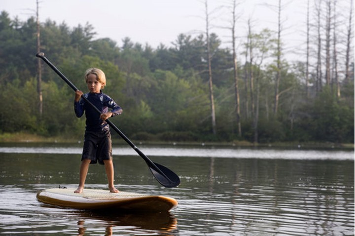 A six-year-old boy rides a stand-up paddleboard on Otter Lake in Greenfield, New Hampshire.