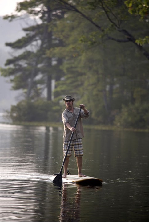 A forty-year-old man on a stand-up paddleboard on Otter Lake in Greenfield, New Hampshire.