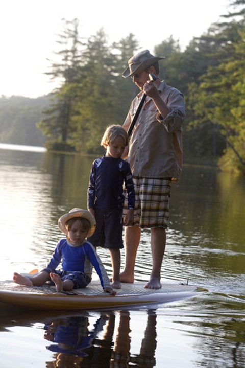 Six-year-old and four-year old brothers ride with their father on a stand-up paddleboard on Otter Lake in Greenfield, New Hampshire.