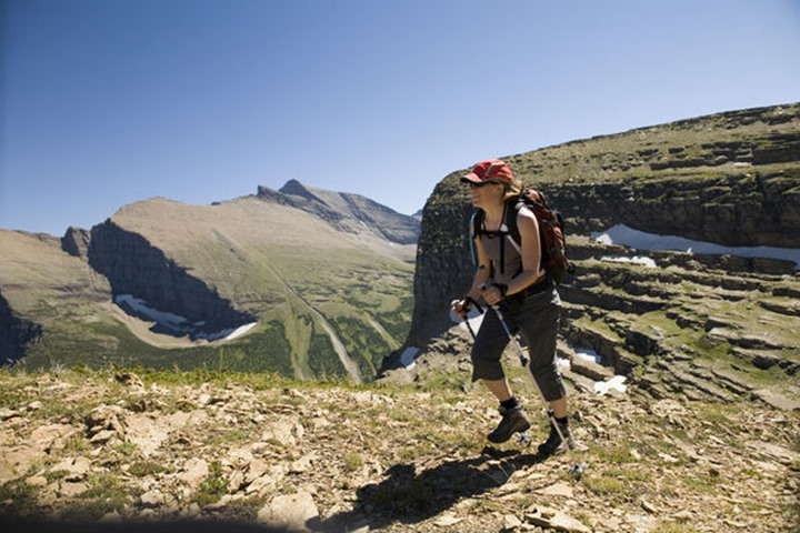 A woman in her early thirties hikes along the Grinnell Glacier trail in Glacier National Park, Montana. The Grinnell Glacier trail is a popular hike in the park, because visitors can walk right up to
