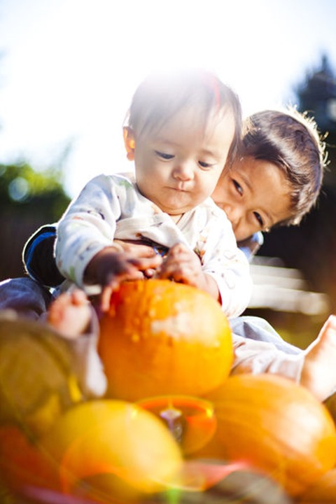 Tuscan Kiyoshi Glass, 3.5 year old Japanese-Amercian boy, hugs his brother, Bridger Hitoshi Glass, as they sit on pumpkins and squash in a red wagon.