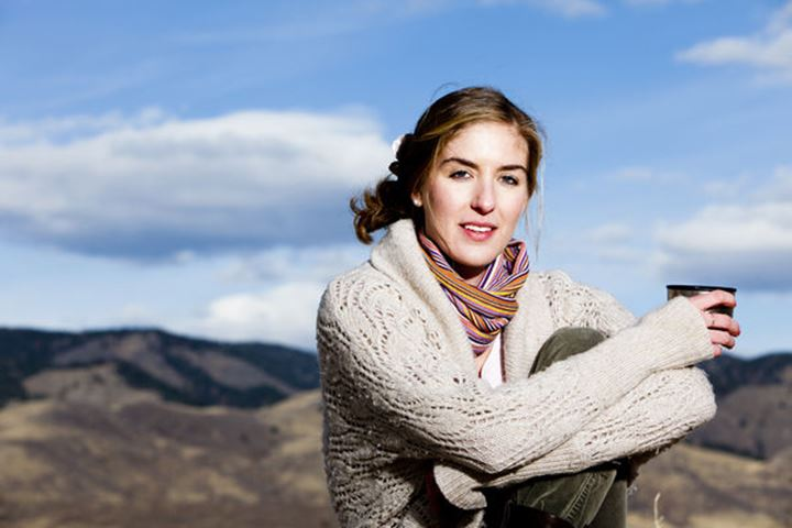 Melissa Lombardi models in layered clothing while sitting on a stool and drinking coffee from a thermos cup, on Bingham Hill, Fort Collins, Colorado.