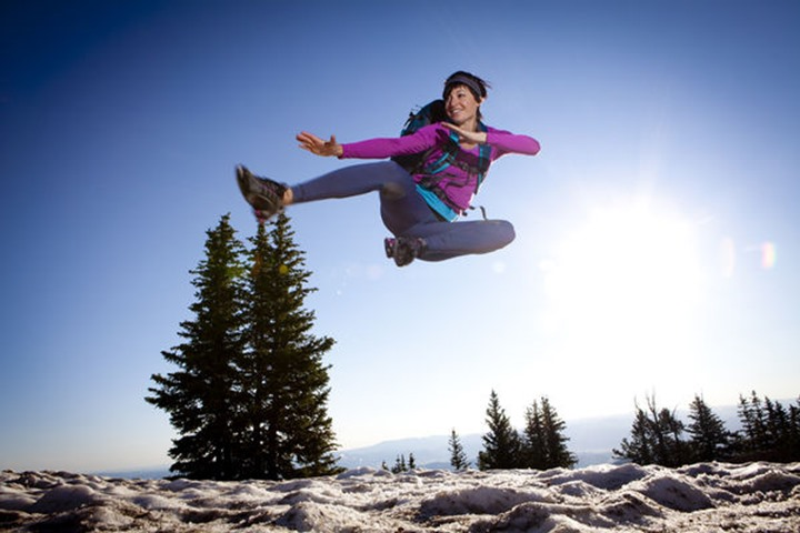 A woman jumping for joy on the Wasatch Crest trail.