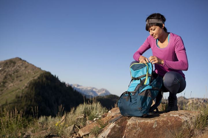 A woman pausing for a snack break on the Wasatch Crest Trail.