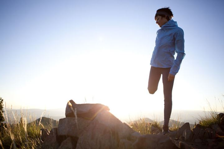 A woman streching before an early morning run on the Wastach Crest Trail.