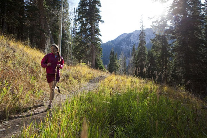 A woman trail running throught the woods of Solitude ski resort.