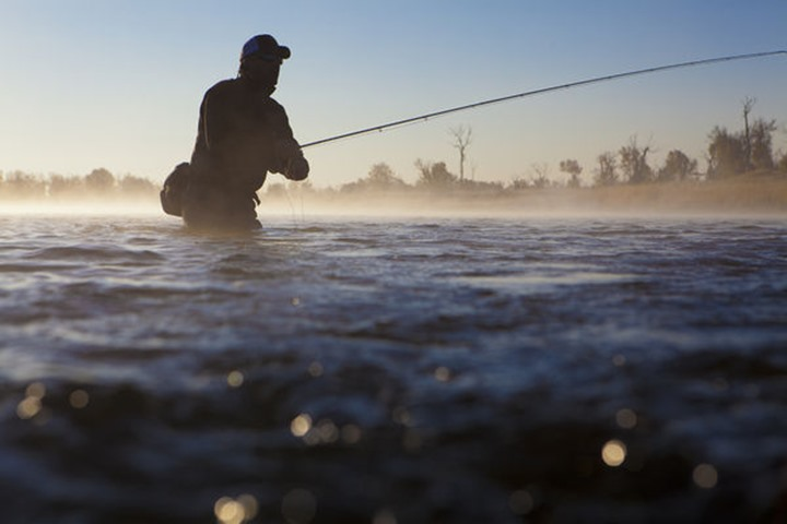 A man fishing in the early morning mist of the Green river.