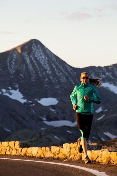 Runner, Jennifer Lee, runs along Trail Ridge Road (12,183 feet) near its apex at sunrise, Rocky Mountain National Park, Colorado.