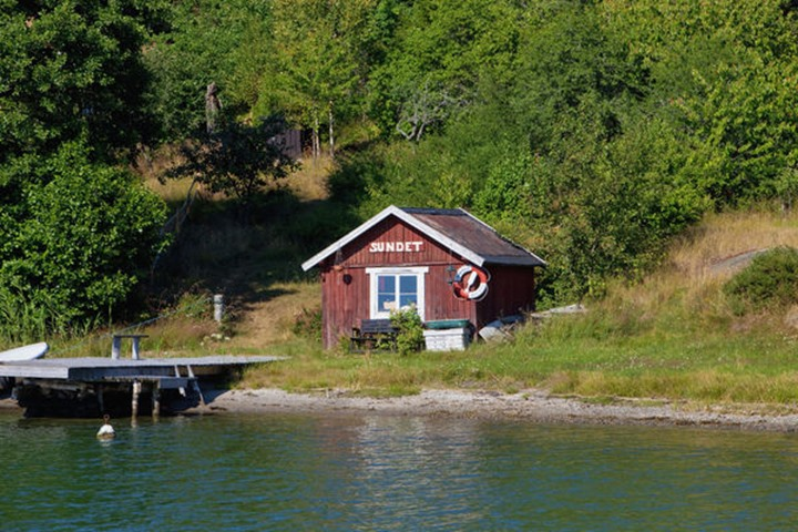 Sweden, Stockholm - Little red house on island in archipelago.