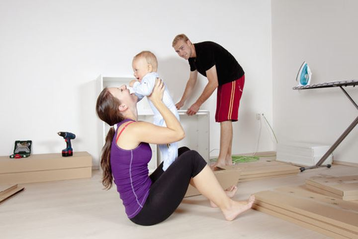 Young Family with a Baby  Moving in a New Apartment