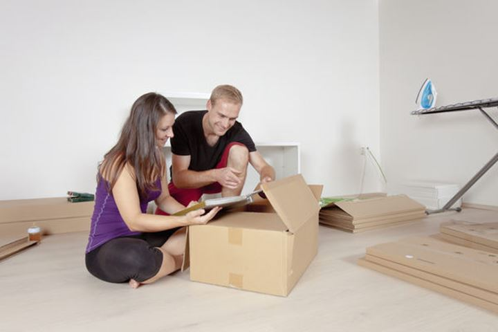 Young Couple Moving, Unpacking, Looking at Old Pictures