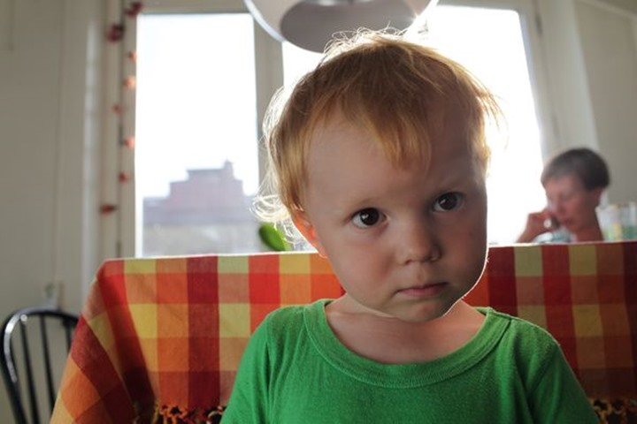 Boy, 2 year, in a kitchen, mother talking on the phone, Sweden.