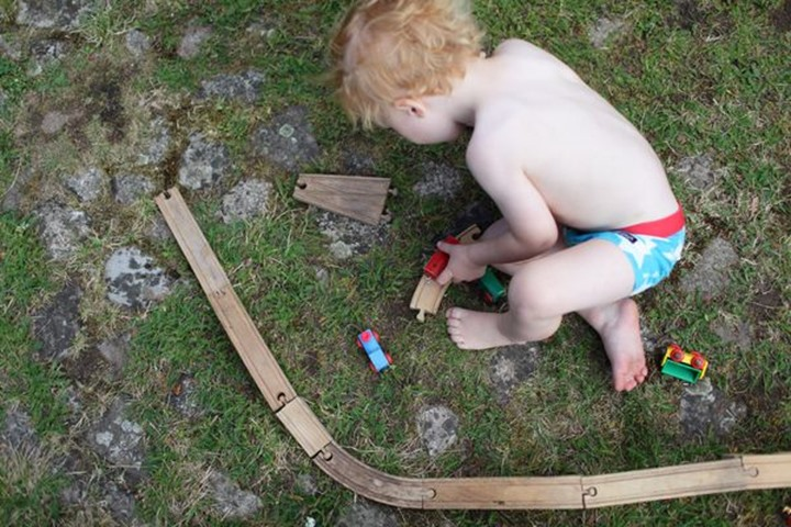 Baby boy playing with a wooden railway, Sweden.