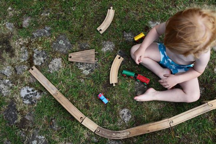 Baby boy building a wooden railway, Sweden.