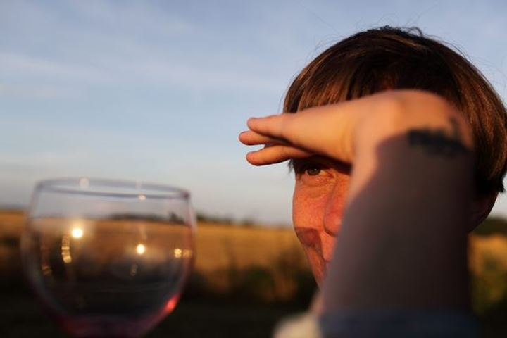 Young adult female, drinking wine, watching sunset, Sweden.