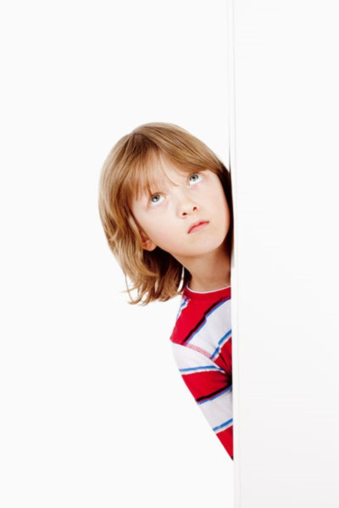 Boy With Blond Hair Peeking Out From Behind A White Board Looking Up