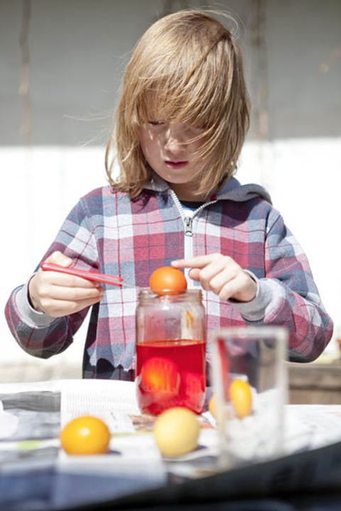 Boy Coloring Easter Eggs by Putting Them in Glasses with Color