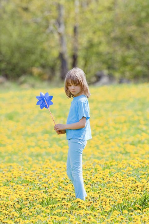 Boy with Pinwheel in a Meadow of Dandelions