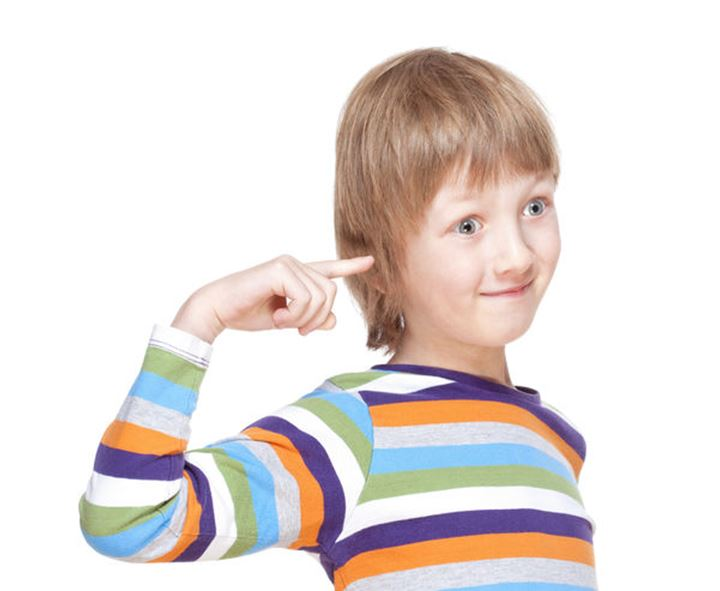 Boy in Colorful Shirt Pointing Finget to his Head - Isolated on White
