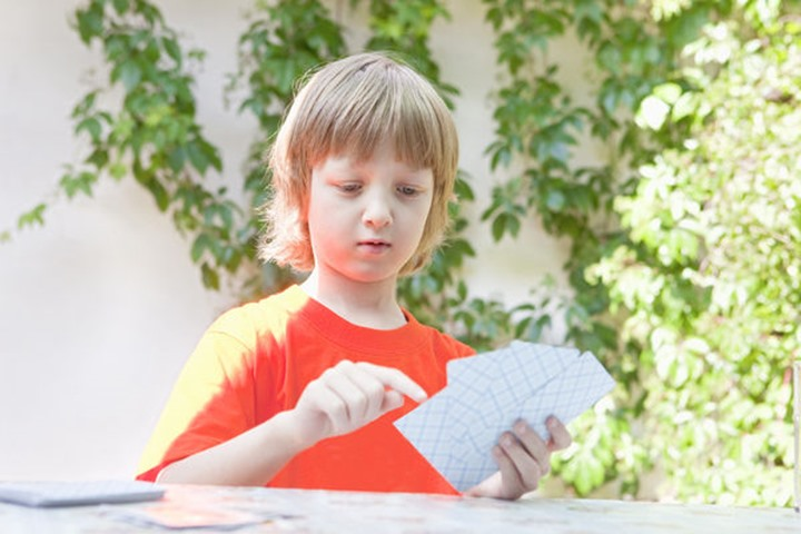 Boy with Blond Hair Playing Cards Outdoors