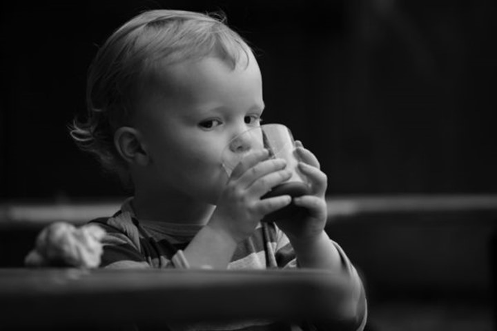 Baby boy drinking milk and eating a bun, Sweden.
