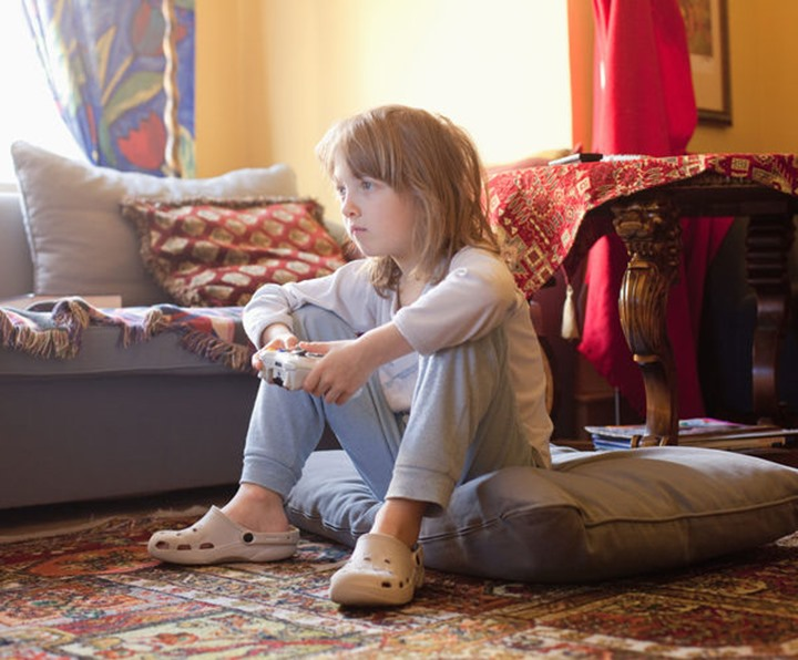 Boy Playing Console Game Sitting on the Floor