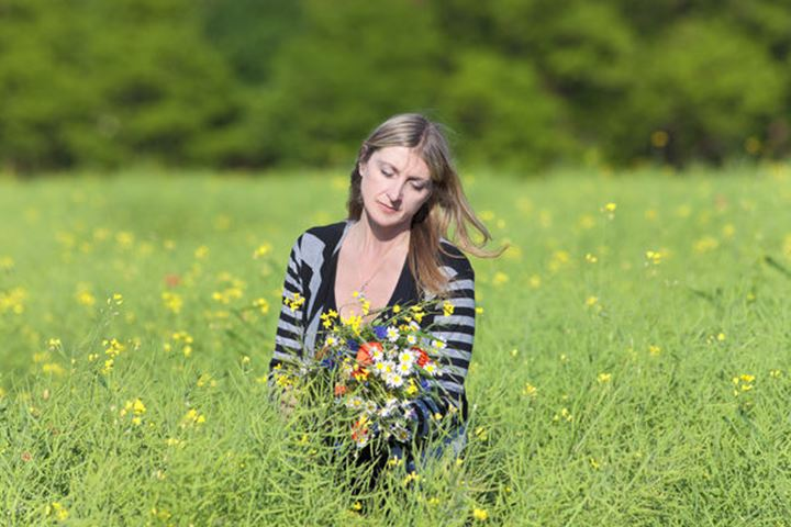 Woman Picking Wild Flowers on the Meadow in Spring