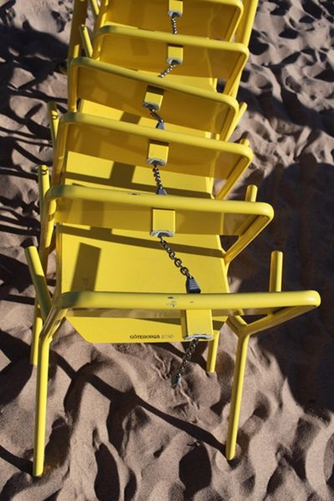 Yellow chairs locked together at a beach, Sweden.