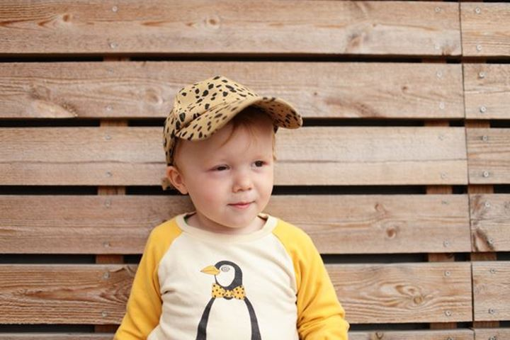 Baby boy standing against a wooden wall, Sweden.