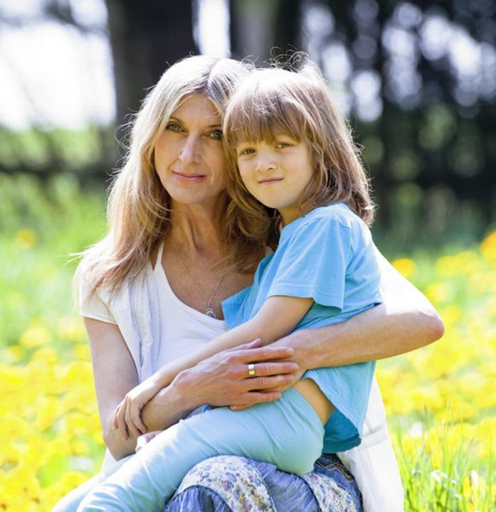 Boy Embracing his Mother, Sitting on her Lap in Garden