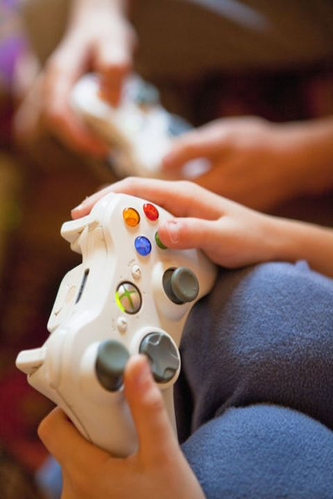 Two Boys Playing Console Game - Closeup of Fingers on Gamepad