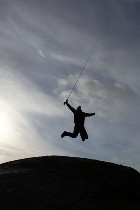 A man holding a fishing rod jumping on a cliff, Sweden.