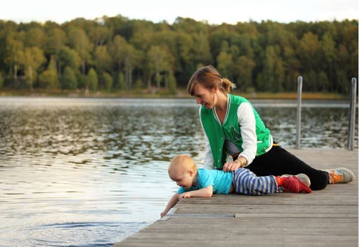 A mother with her baby boy playing by a lake, Sweden.