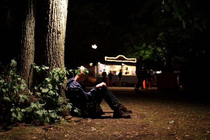 A young man resting against a tree in a park, night, Sweden.