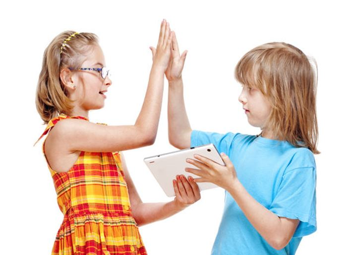 Two Children Doing High Five Gesture after Winning a Game on Tablet