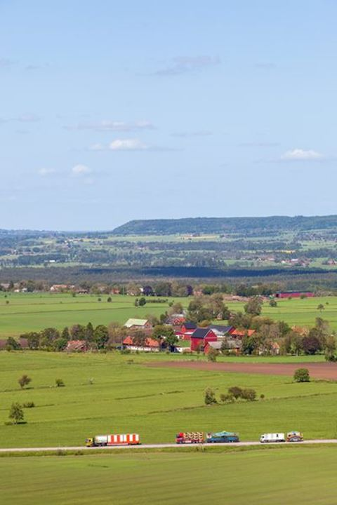 View of agricultural landscapes in Sweden with Circus trucks on the road