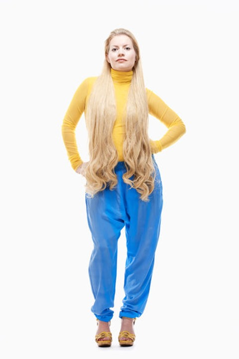 Young Woman with Long Blond Hair in Yellow Top and Blue Pants.